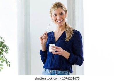 Portrait of beautiful young woman looking at camera while eating yogurt at home.