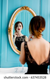 portrait of beautiful young woman looking at herself in the wonderful mirror