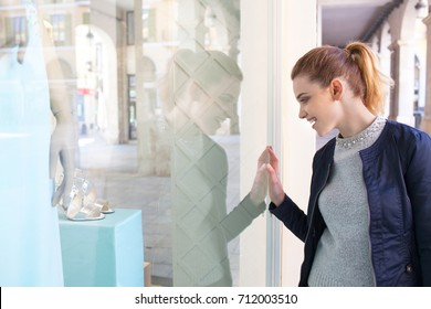 Portrait of beautiful young woman looking at shop window with shoes fashion clothing manikins, glass reflections expensive store, city street outdoors. Consumer female smiling, recreation lifestyle.