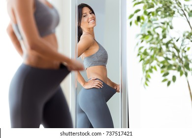 Portrait of beautiful young woman looking herself reflection in mirror at home.