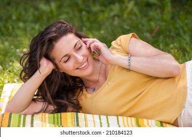 Portrait of a beautiful young woman lying on the grass at park and talking on phone