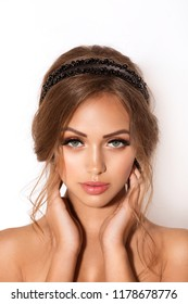 Portrait of beautiful young woman with makeup and by a beautiful hair-do by the decorated stylish bijouterie