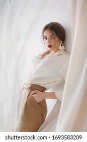 Portrait of beautiful young woman with makeup in fashion white clothes