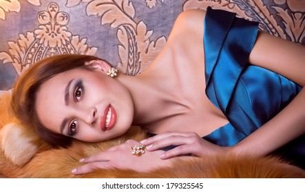 Portrait of beautiful young woman with makeup and with jewelry precious decorations.