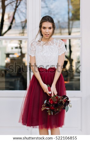 b49ec14d0 Portrait beautiful young woman in marsala tulle skirt on street. She holds  bouquet of flowers