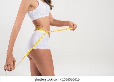 Portrait of beautiful young woman measuring her figure size with tape measure