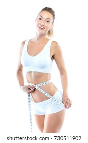 Portrait of beautiful young woman measuring her slim body over white background.