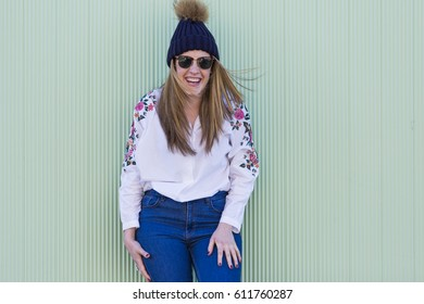 portrait of a beautiful young woman with modern sunglasses and hat, she is smiling. Green background. Lifestyle. Casual clothing