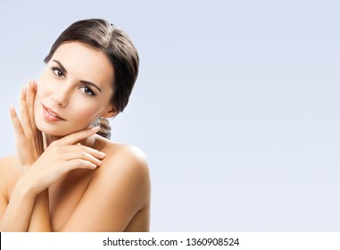 portrait of beautiful young woman with naked shoulders, on grey background, with big copy space area, for some text, advertising or slogan