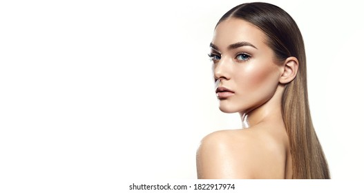 Portrait of a beautiful young woman with natural makeup and well-groomed hair on a white background in the studio. Smooth, well-groomed tanned skin.