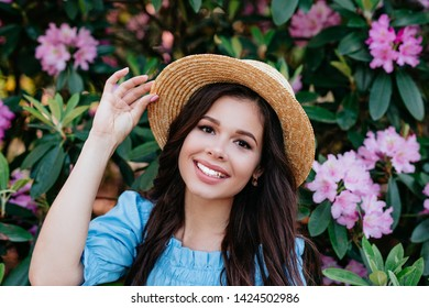 Portrait of beautiful young woman near blooming bush outdoors