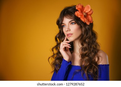 portrait of a beautiful young woman on a yellow background, beautiful flower in her hair, delicate natural make-up.