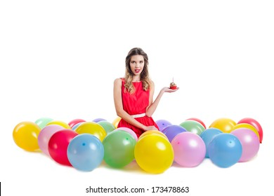 Portrait of beautiful young woman  on birthday party, sitting with with colorful balloons  and holding cupcake, isolated on white background
