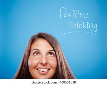 Portrait of a beautiful young woman on a blue background is thinking positive.