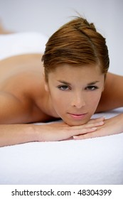 Portrait of beautiful young woman on a massage bed