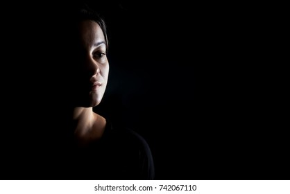 Portrait of a beautiful young woman over black background.