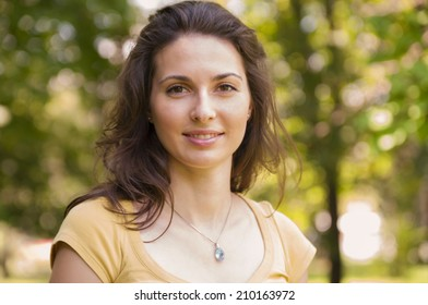 Portrait of a beautiful young woman at park looking at the camera