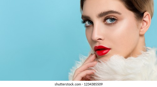 Portrait of beautiful young woman with perfect young skin, red matt lips in white fur.  Model with bright scarlet color makeup and sparkled manicure.  Winter seasonal beauty. Copyspace.