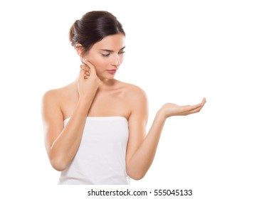 Portrait of beautiful young woman with perfect skin holding something on her hand. Beauty woman showing a beauty product on her hand isolated on white background. Girl showing with copy space.