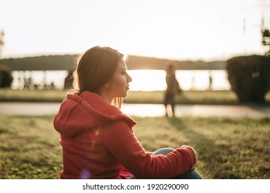 Portrait of a beautiful young woman in a pink sports hoodie, jeans and a backpack sitting on the green grass in the park at sunset. European girl in nature. Travel with a backpack alone.