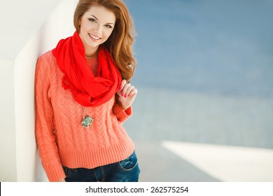 Portrait of beautiful young woman in pink sweater and red scarf. Beautiful woman in a sweater in the fall. Portrait of beautiful young woman walking outdoors in the city