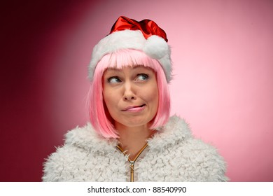 Portrait of a beautiful young woman in pink wig wearing christmas clothes over red background.