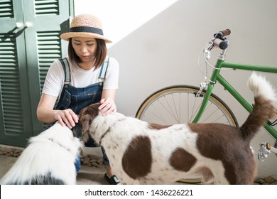 Portrait of beautiful young woman playing with dog at house