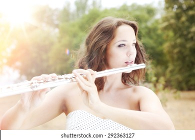 Portrait of Beautiful Young Woman Playing The Silver Flute in the Perfect Sunny Autumn Day