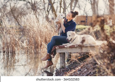 Portrait of beautiful young woman playing with dog by the river. portrait of Young girl sitting on the bridge with her dogs retrievers. woman with puppies. Girl with dogs.