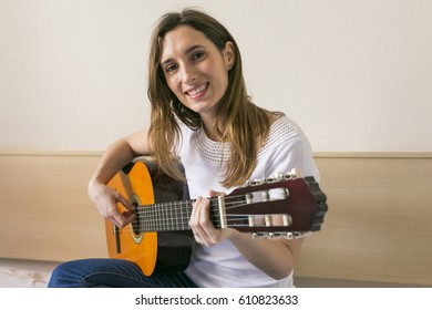 portrait of a beautiful young woman playing guitar at home and having fun. Daytime. LIfestyle