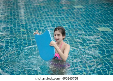 portrait of beautiful young woman in the poolside swimming  during  holiday