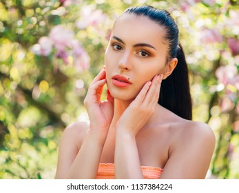 Portrait of beautiful young woman posing in spring blossoming magnolia garden