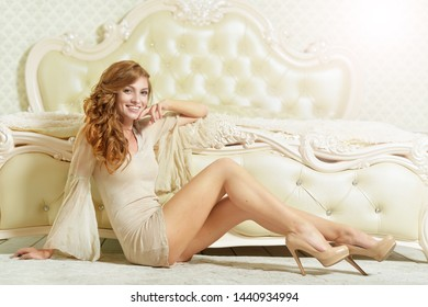 Portrait of beautiful young woman posing near bed