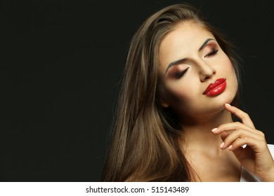 Portrait of beautiful young woman with professional makeup on dark background