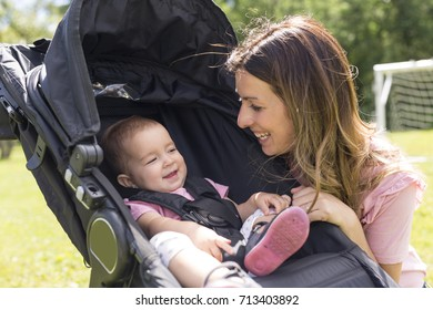 Portrait of beautiful young woman pushing baby carriage in the park
