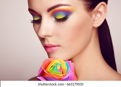 Portrait of beautiful young woman with rainbow rose. Bright colors. Long eyelashes, vivid colorful eyeshadows. Rainbow make up. Multicolored flowers