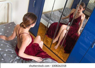 Portrait of beautiful young woman in red dress with naked back, sitting on bed in front of the mirror, beauty fashion concept