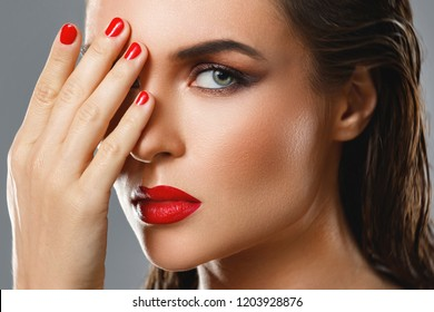 Portrait of beautiful young woman with a red lipstick and nail polish on gray background in studio