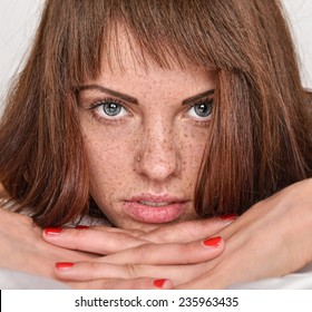 Portrait of the beautiful young woman with red hair and freckles. She is lying in the bed