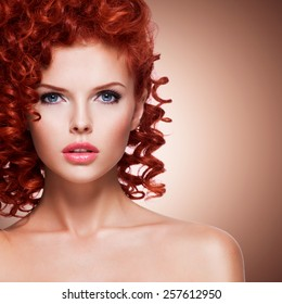 Portrait of beautiful young woman with red curly hair  on beige background.