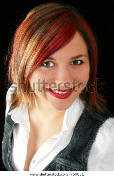 Portrait of a beautiful young woman with red, blonde and black highlights in her hair.  Great smile.