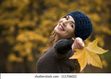 Portrait of a beautiful young woman relaxing with arms open and enjoying the fall season