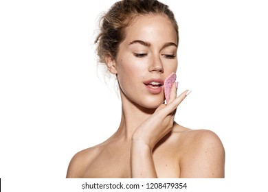 Portrait of beautiful young woman removing makeup with pink soft sponge. Good-looking model with clean skin on white background. Beauty and skincare concept