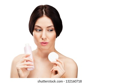 A portrait of a beautiful young woman removing her make up, isolated on white background