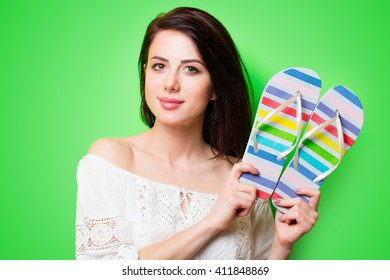 portrait of the beautiful young woman with sandals on the green background