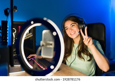 Portrait of a beautiful young woman saying hello to her online viewers during a live stream with a smartphone and a ring light. Smiling female gamer playing a video game in a gaming PC