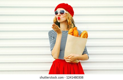 Portrait beautiful young woman sends sweet air kiss wearing red beret holding in hands paper bag with long white bread baguette on white wall background