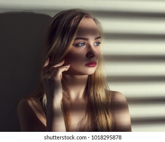Portrait of beautiful young woman with shadows from blinds.