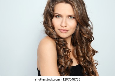 Portrait of beautiful young woman with shiny wavy hair on color background. Space for text