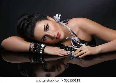Portrait of beautiful young woman with shiny black hair and bright makeup sitting near glass table. Over dark background